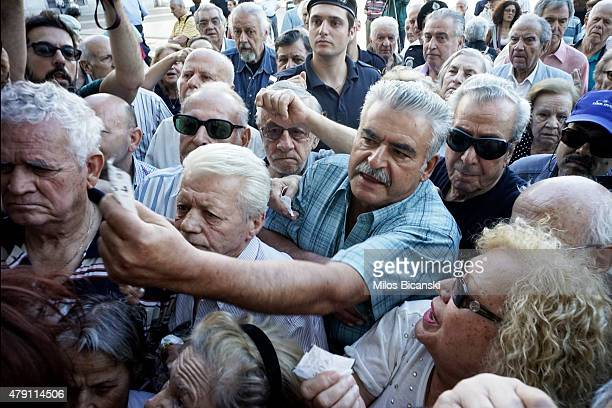 Pensioners line up outside a National Bank branch on July 1 2015 in Athens Greece Bank branches around Greece are opened on Wednesday to allow...