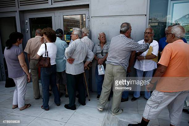 Pensioners queue outside a closed National Bank of Greece SA bank branch in the hope that it might open in Athens Greece on Monday June 29 2015...