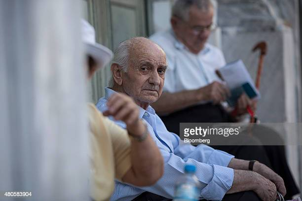 Pensioners sit and wait to collect their pensions outside a Bank of Greece SA bank branch in Athens Greece on Monday July 13 2015 Greece has been in...