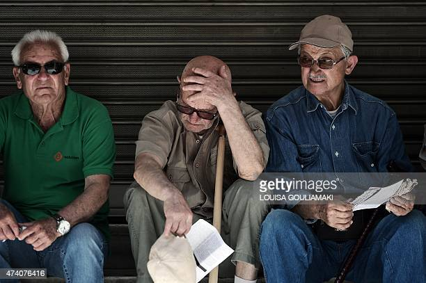 Pensioners sit outside the Ministry of Health in Athens during a 24hour strike by health workers and doctors on May 20 2015 Health sector workers...
