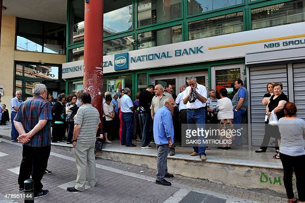 Pensioners stand outside a closed branch of the Greek National bank in Thessaloniki on June 29 2015 as as Greece ordered its banks to shut for one...