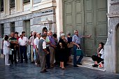 Pensioners wait in front of the gate of the National Bank of Greece as they wait to withdraw money with a maximum of 120 euros in Athens July 7 2015...