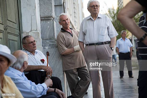Pensioners wait to collect their pensions outside a Bank of Greece SA bank branch in Athens Greece on Monday July 13 2015 Greece has been in...
