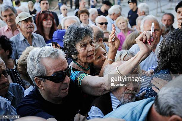 Pensioners wave ticket numbers as they try to get inside a National Bank of Greece SA bank branch to collect their pensions in Athens Greece on...