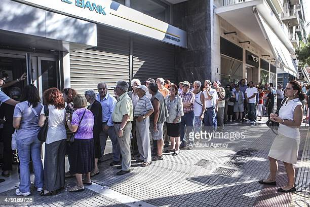 Pensioners without ATM cards wait in queue outside a bank branch to withdraw money from their pension funds on July 02 2015 in Athens Greece