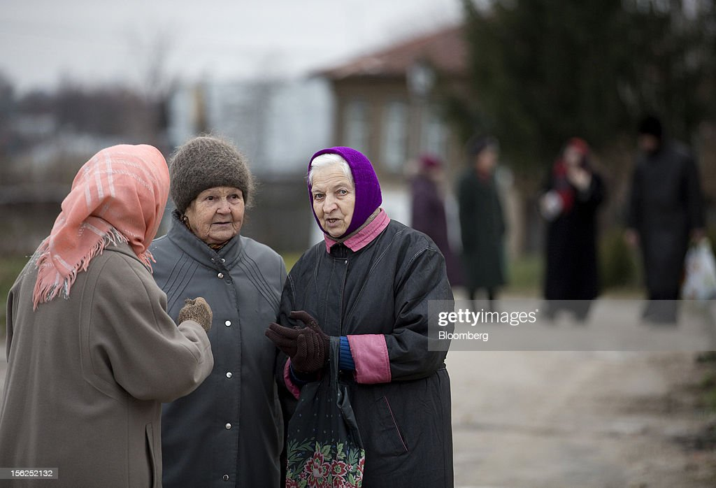 Pensioners wrapped up against the cold chat after meeting at the local market in Suzdal, Russia, on Sunday, Nov. 11, 2012. Russia has one of the world's lowest retirement ages, set in 1932 during the Stalin era. Photographer: Andrey Rudakov/Bloomberg via Getty Images