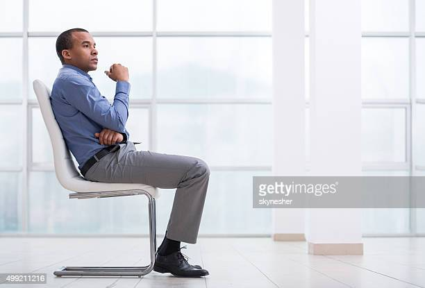 Pensoso uomo d'affari americano africano seduto su una sedia.