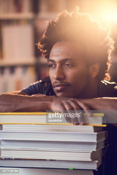 Pensive African American man relaxing on stack of books.