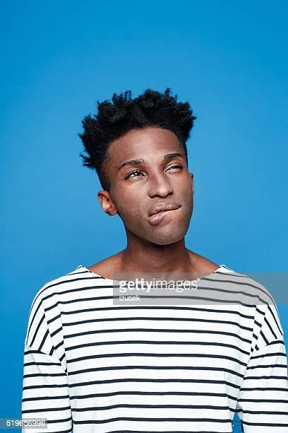 Pensive afro american guy, studio portrait against blue background