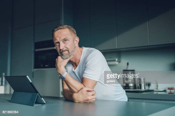 pensive bearded midaged man with tablet at kitchen table