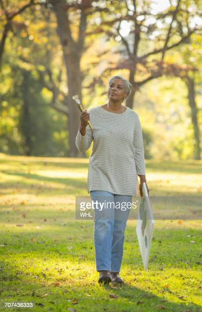 Pensive Black woman carrying paintbrushes and canvas in park