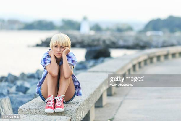 Pensive blond woman sitting on beach