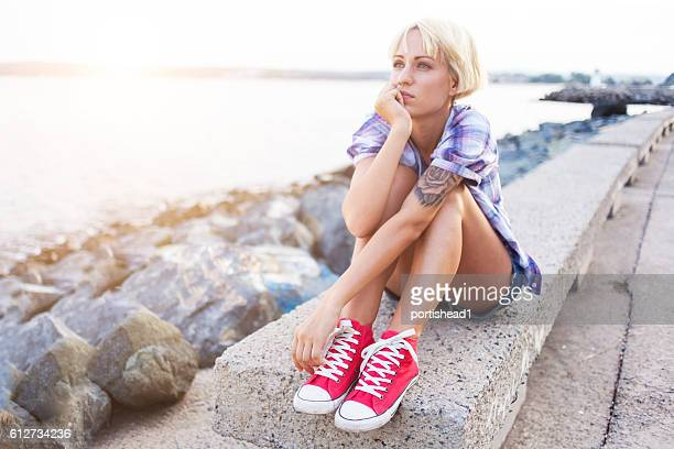 Pensive blond woman sitting on parapet next to the sea