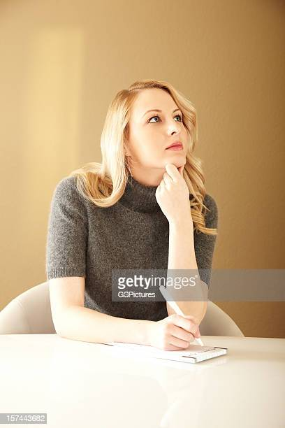 Pensive Blonde Woman Writing a To Do list