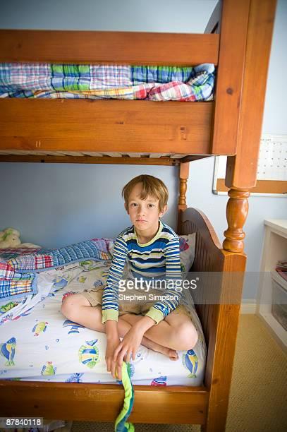 pensive boy sits cross-legged in his bedroom