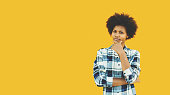 Young black female teenager in plaid shirt is making pensive emotional face while standing in front of isolated solid yellow background with copy space place for logo, text or your advertising message