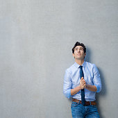 Young businessman leaning against grey wall with palms joint. Pensive handsome man looking up and thinking with copy space. Thoughtful businessman thinking of a new idea or strategy in a grey backgrou