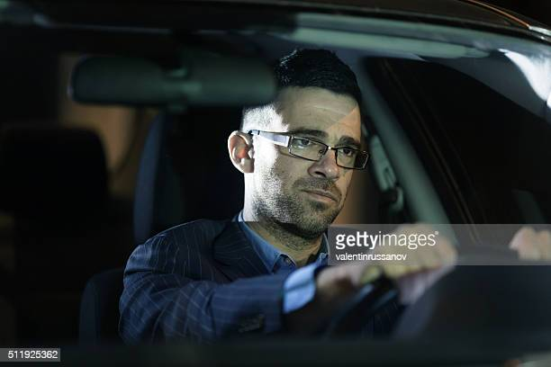 Pensive businessman driving his car by night