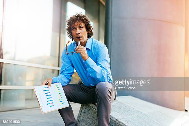 Pensive businessman holding business charts and graphs