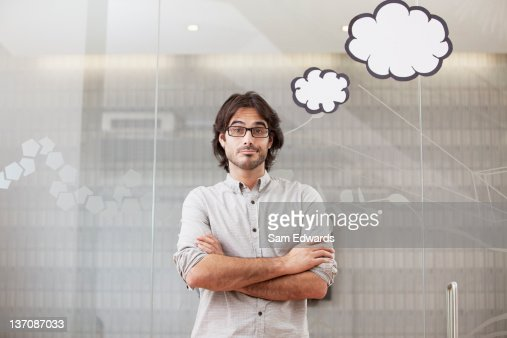 Pensive businessman looking up at thought bubbles overhead : Stock Photo