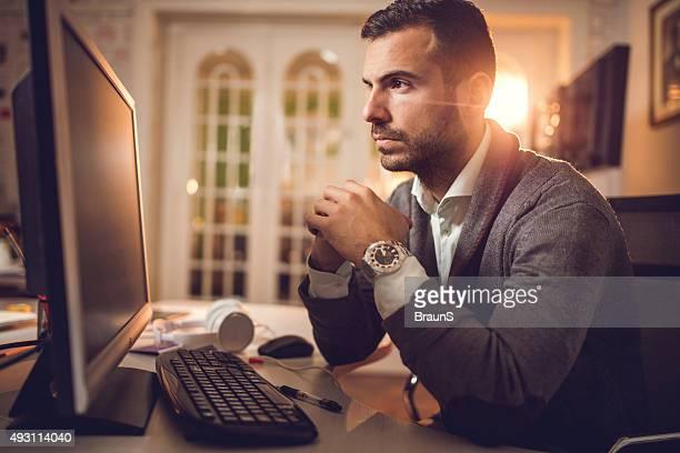 Nachdenklich Geschäftsmann liest etwas von computer im Büro.