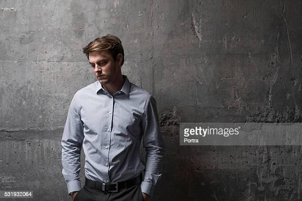 Pensativo hombre de negocios de pie contra la pared de cemento