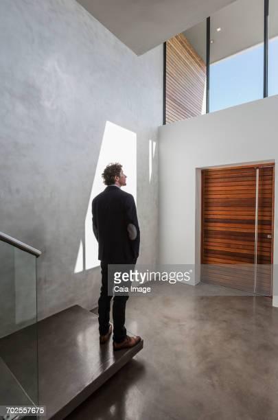 Pensive businessman standing in modern home showcase interior foyer