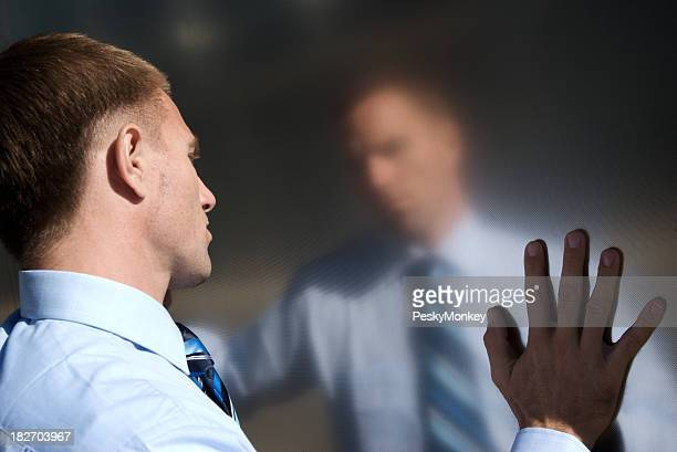 Pensive Businessman Stands Touching Reflection