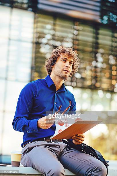 Pensive businessman using coffee break for data analysis
