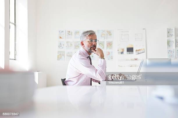 Pensive businessman with laptop at his desk in an office