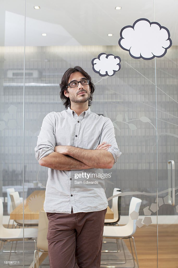 Pensive businessman with thought bubbles overhead : Stock Photo