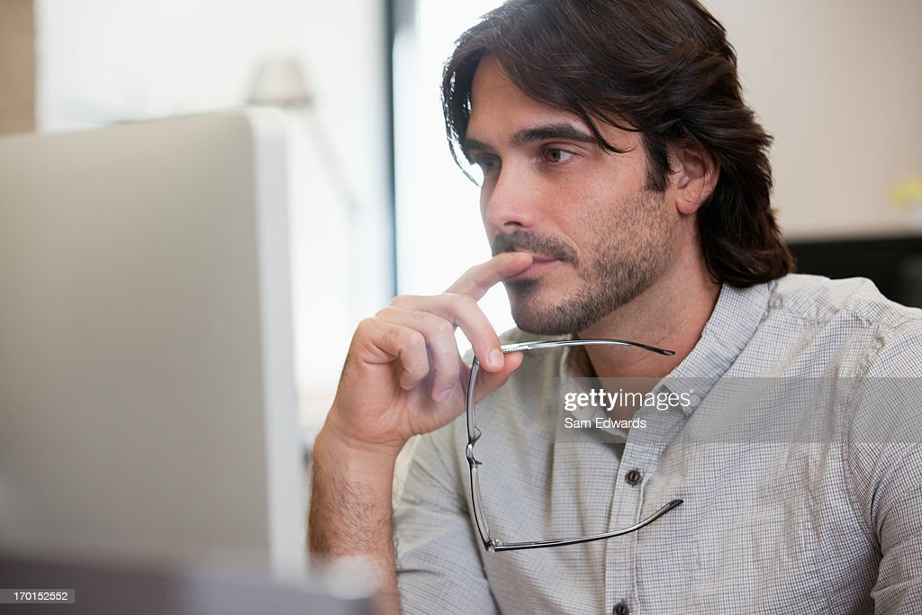 Pensive businessman working on computer in office : Stock Photo