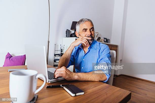Pensive businessman working with laptop at home office