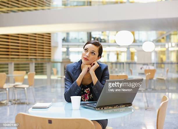 Pensive businesswoman at cafeteria table with laptop