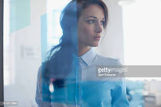 Pensive businesswoman in office window