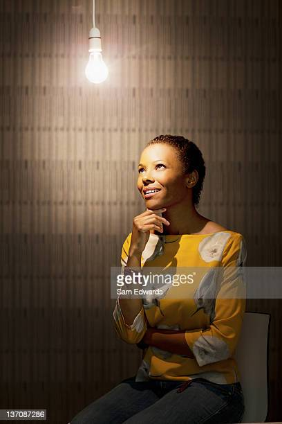 Femme d'affaires pensif assis sous ampoule éclairée