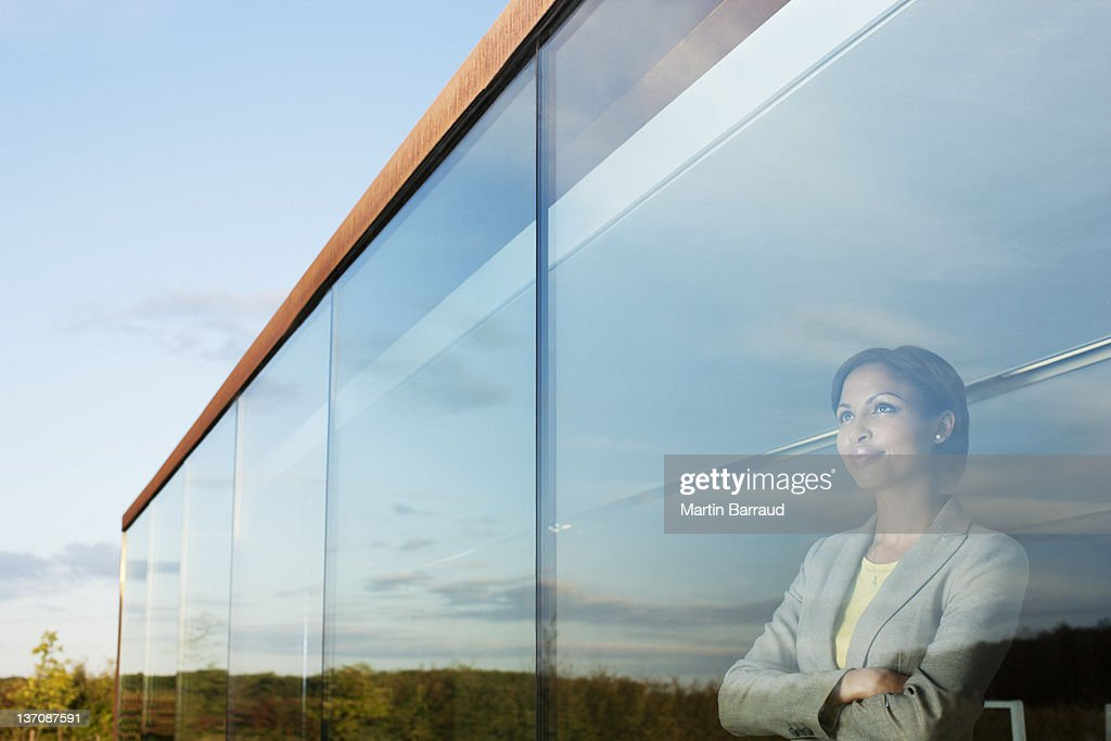 Pensive businesswoman with arms crossed in office window