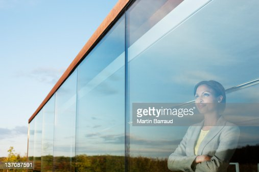 Pensive businesswoman with arms crossed in office window : Stock Photo