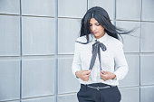 Pensive calm businesswoman with hair blown by wind looking down while walking. Sad young Hispanic woman adjusting bow of blouse thinking of life. Beautiful woman concept