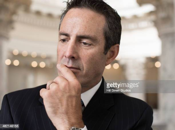 Pensive Caucasian politician in government building