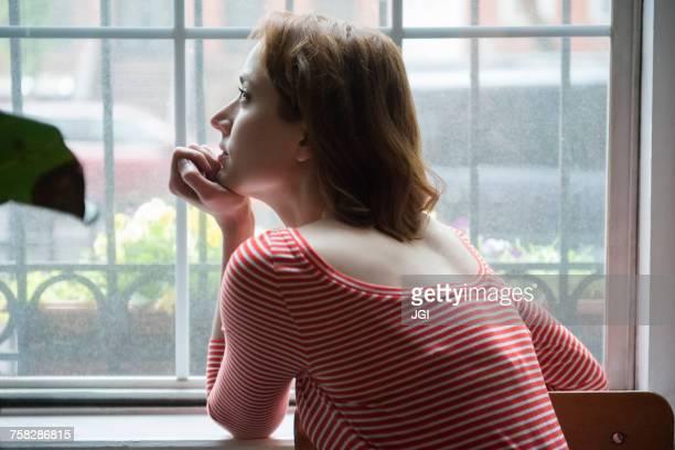 Pensive Caucasian woman daydreaming near window