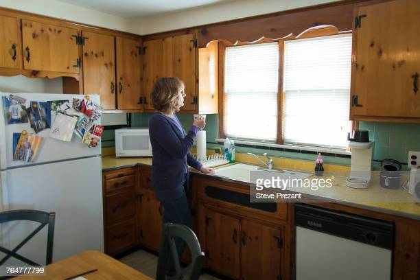 Pensive Caucasian woman drinking coffee in kitchen