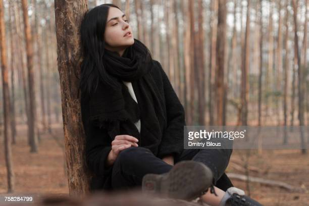 Pensive Caucasian woman sitting on log in forest
