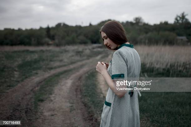 Pensive Caucasian woman standing near dirt road