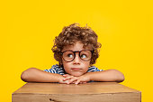 Portrait of curly boy in glasses leaning on box looking away pensively on orange background.
