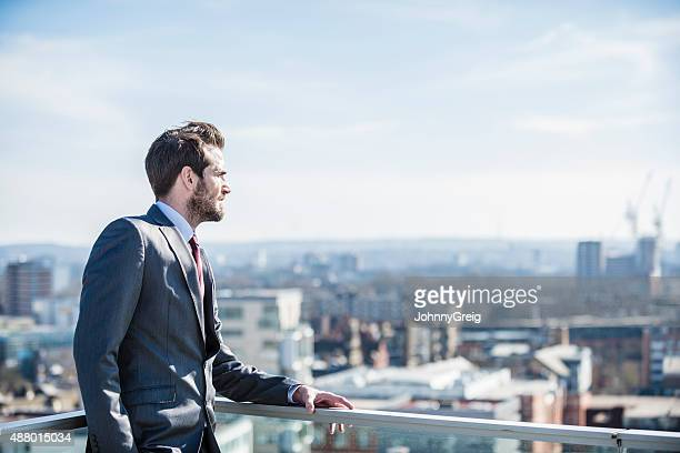 Pensive city businessman looking to horizon