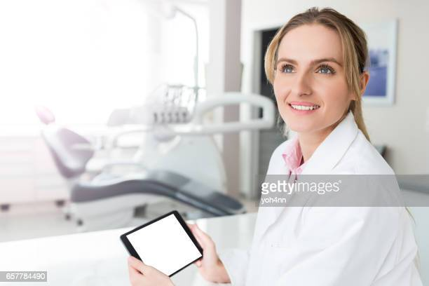 Pensive dentist with white screen tablet