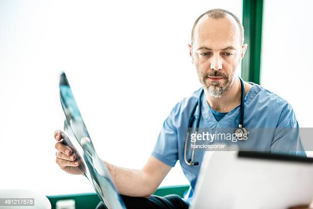 Pensive doctor looking the xray on the tablet
