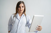 Pensive female Caucasian specialist in lab coat holding tablet and looking at you. Portrait of pretty dark-haired doctor putting hand in pocket of uniform. Medical consulting concept