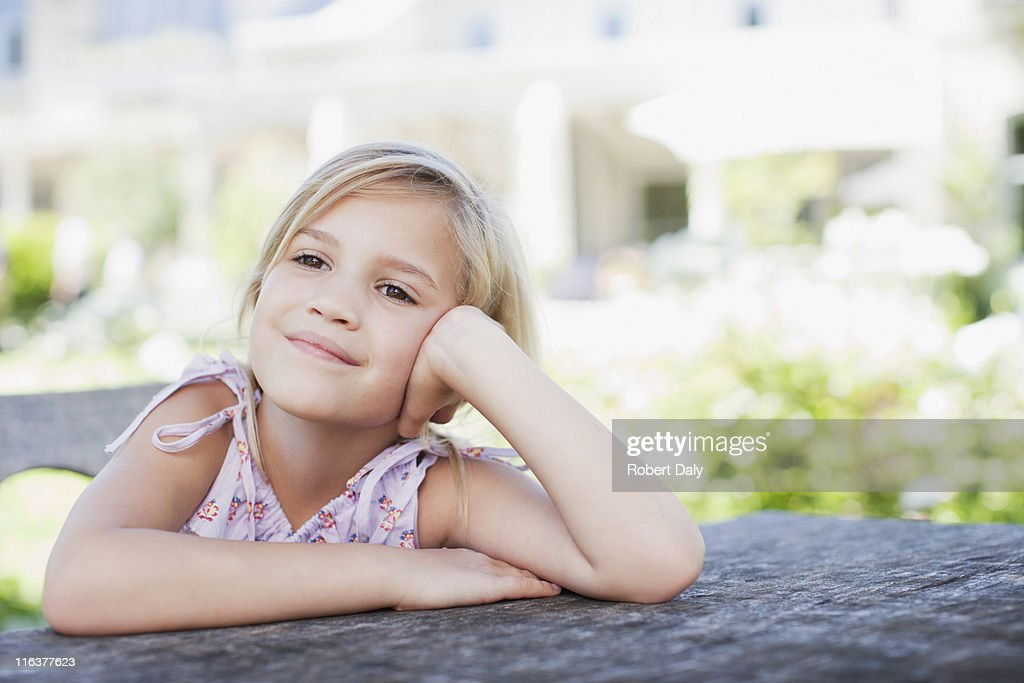 Pensive girl sitting at table outdoors : Stock Photo